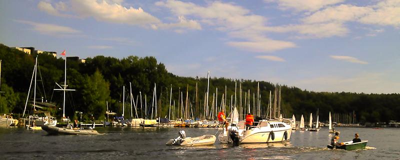 2 rote Westen auf ehemaligem Segelboot mit Dhingi im Schlepp