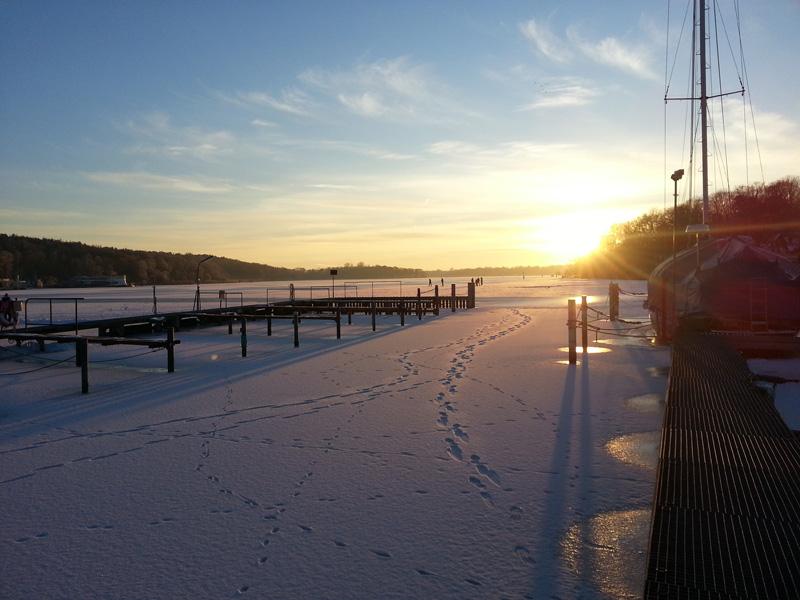 Blick auf den Breiten (Eis) See mit Schlittschuhläufern, im Vordergrund leere Boxen und eine eingefrorene Segelyacht