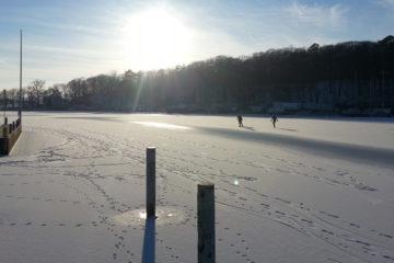 Eisläufer auf dem Stössensee vor blauem Himmel, strahlender Sonne und teils leeren Liegeplätzen und Dalben